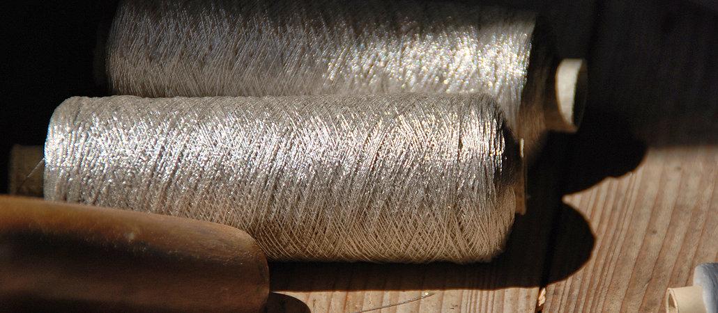 Zwei silbrig glänzende Garnrollen in Nahaufnahme auf einem Holztisch liegend