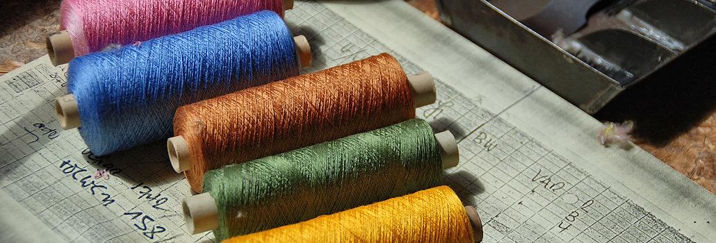 Farbige Garnrollen einer Handmaschinenstickerei in der Schweiz_Sie liegen auf einem Holztisch auf einer Zeitung