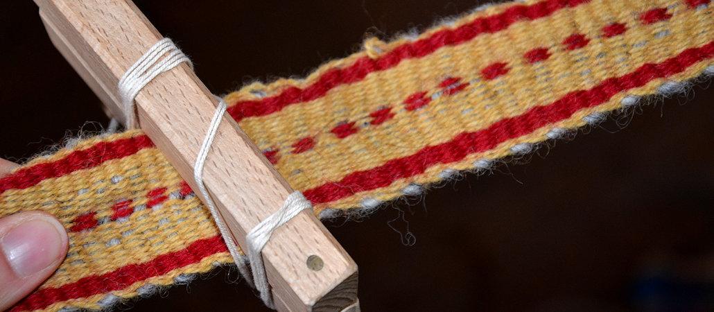 Webkamm aus Holz mit einem in Gelb und Rot gewebten Banden Kammweben Schweden