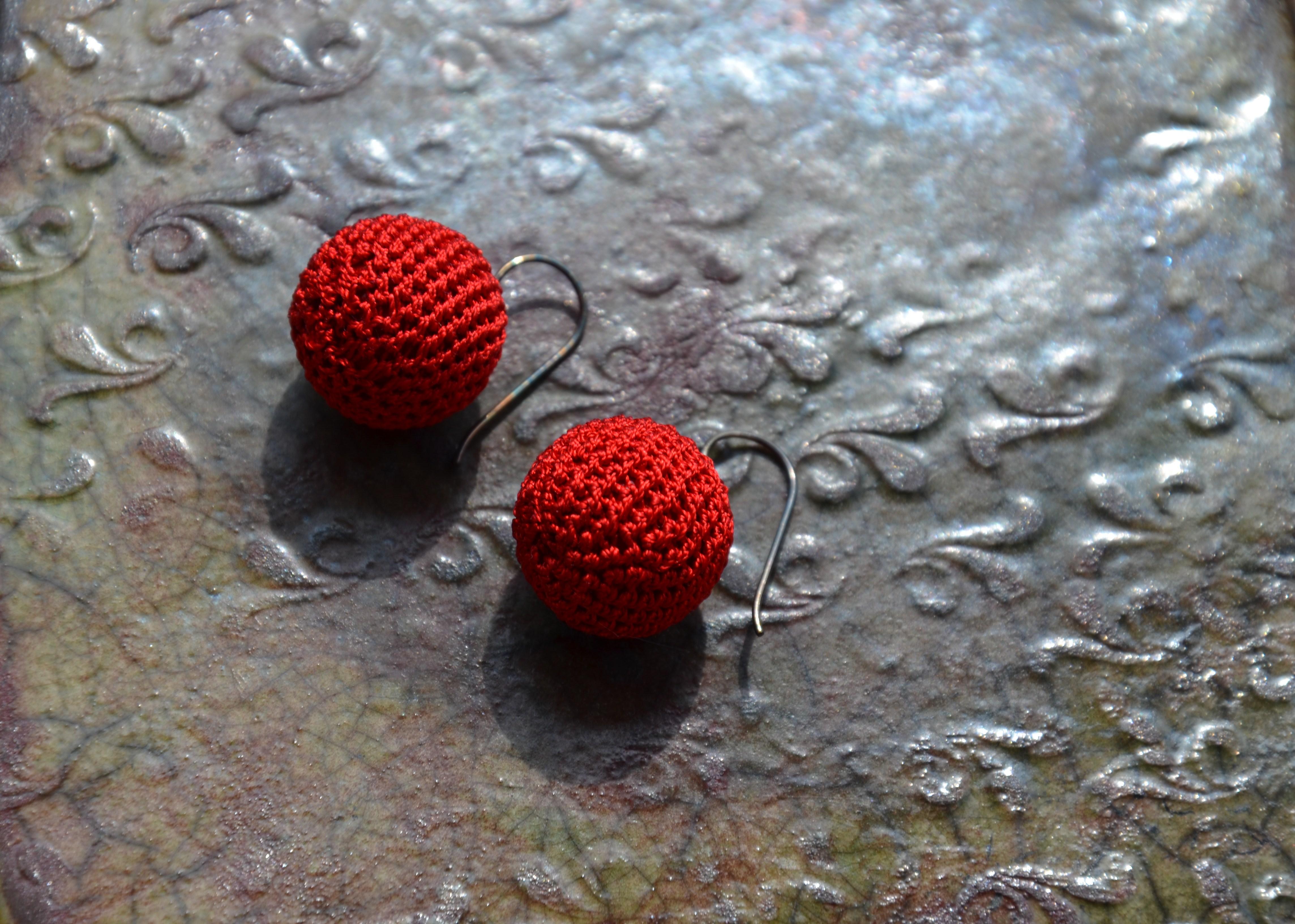 Auf einer mit Reliefdruck verzierten Kachel liegt ein Paar Ohrhänger. Diese sind aus rotem Baumwollgarn sehr fein in Form einer Kugel gehäkelt. Die Kugeln hängen an je einem Silberhaken.